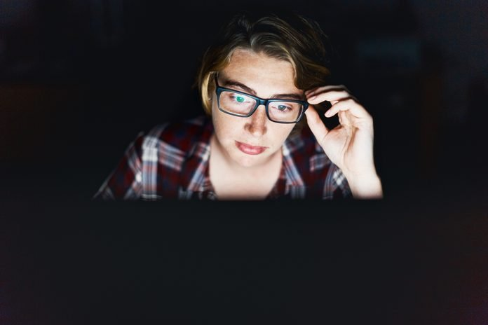 Serious young woman, lit by monitor against black, adjusts spectacles