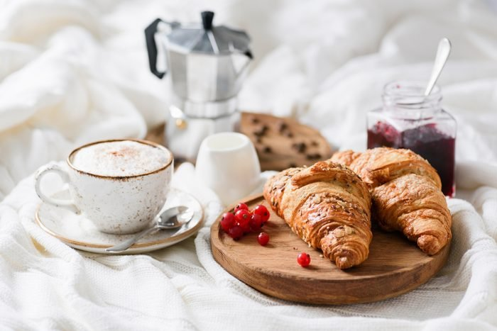 Breakfast in bed with croissants, coffee and jam