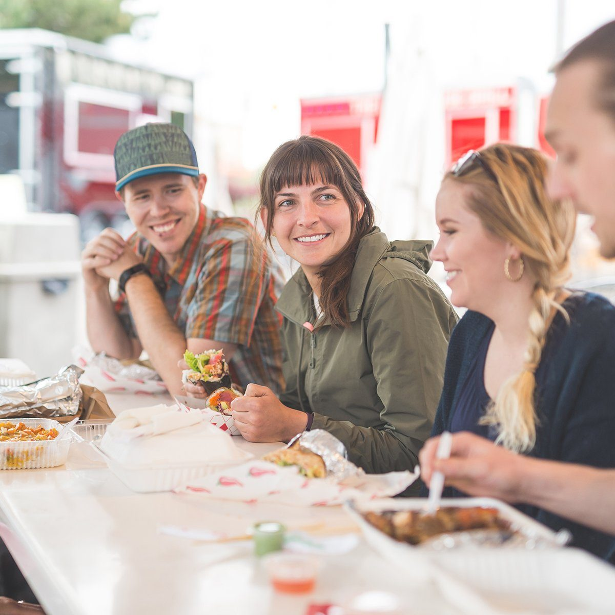 Group of hipster friends in their 20s and 30s enjoy lunch at an outdoor food cart. They are smiling, talking, and enjoying their to-go food at the picnic table.