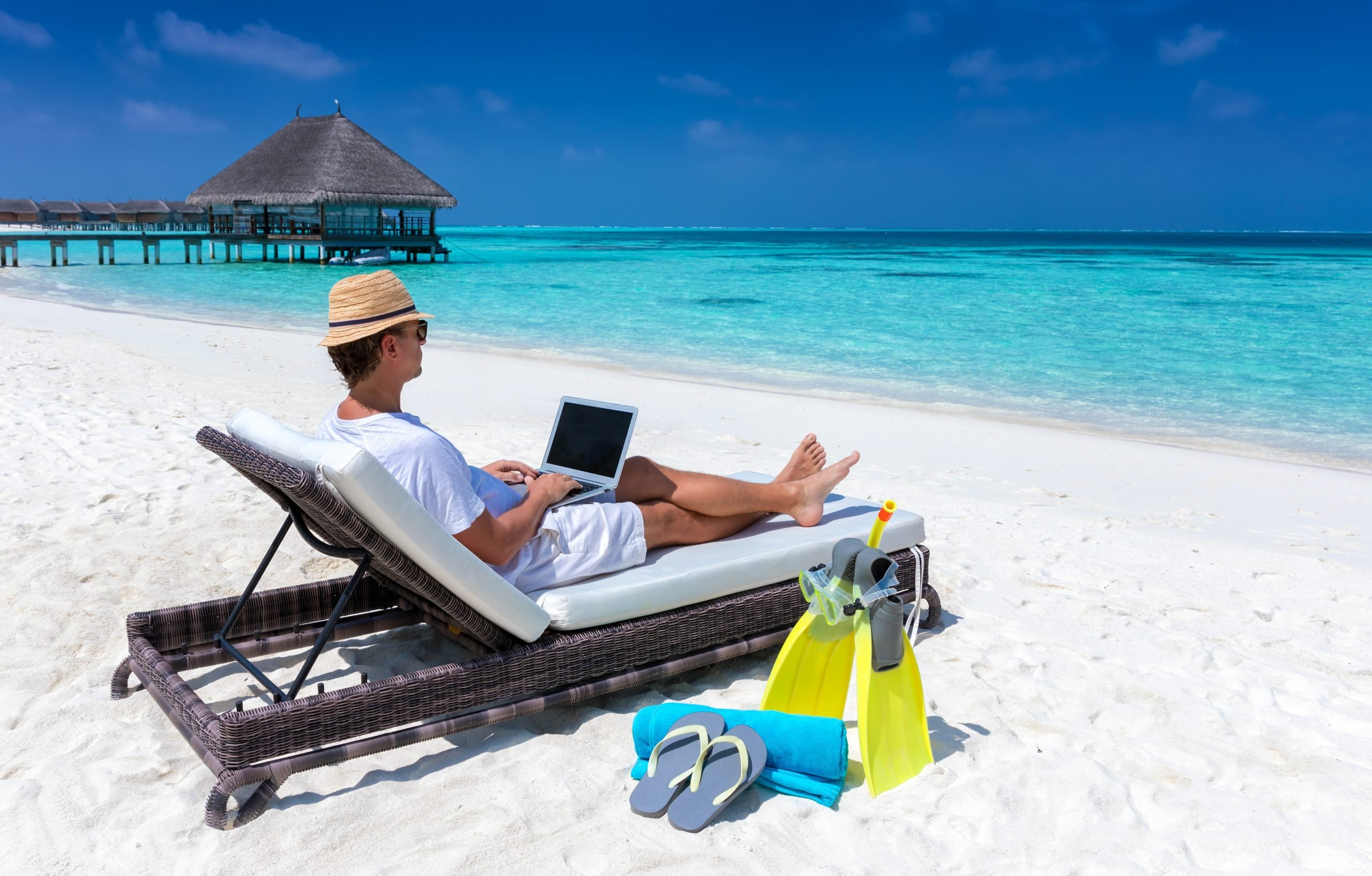 Traveler man sits on a tropical beach with his laptop and works