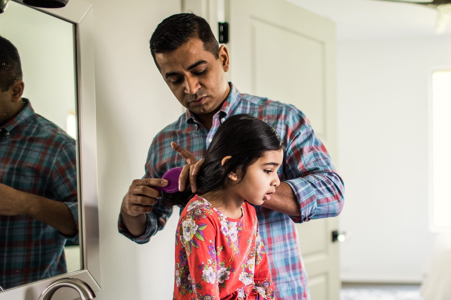 Father brushing daughters hair in bathroom