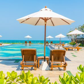 Lounge Chairs With Parasol By Swimming Pool Against Clear Sky