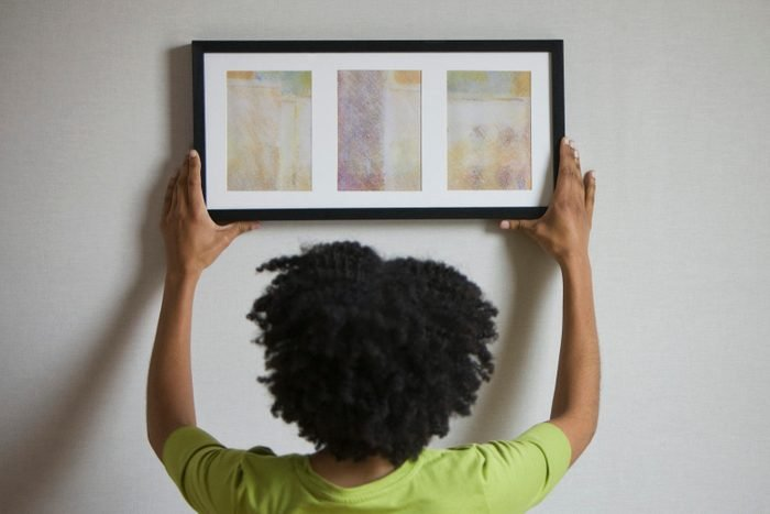 Mixed race woman hanging picture on wall