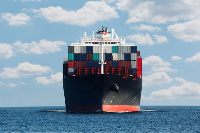 container ship against blue sky with clouds