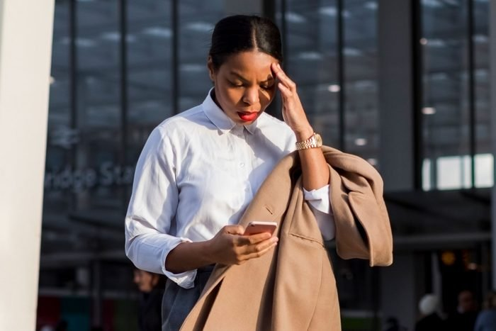Businesswoman looking at smartphone with panic