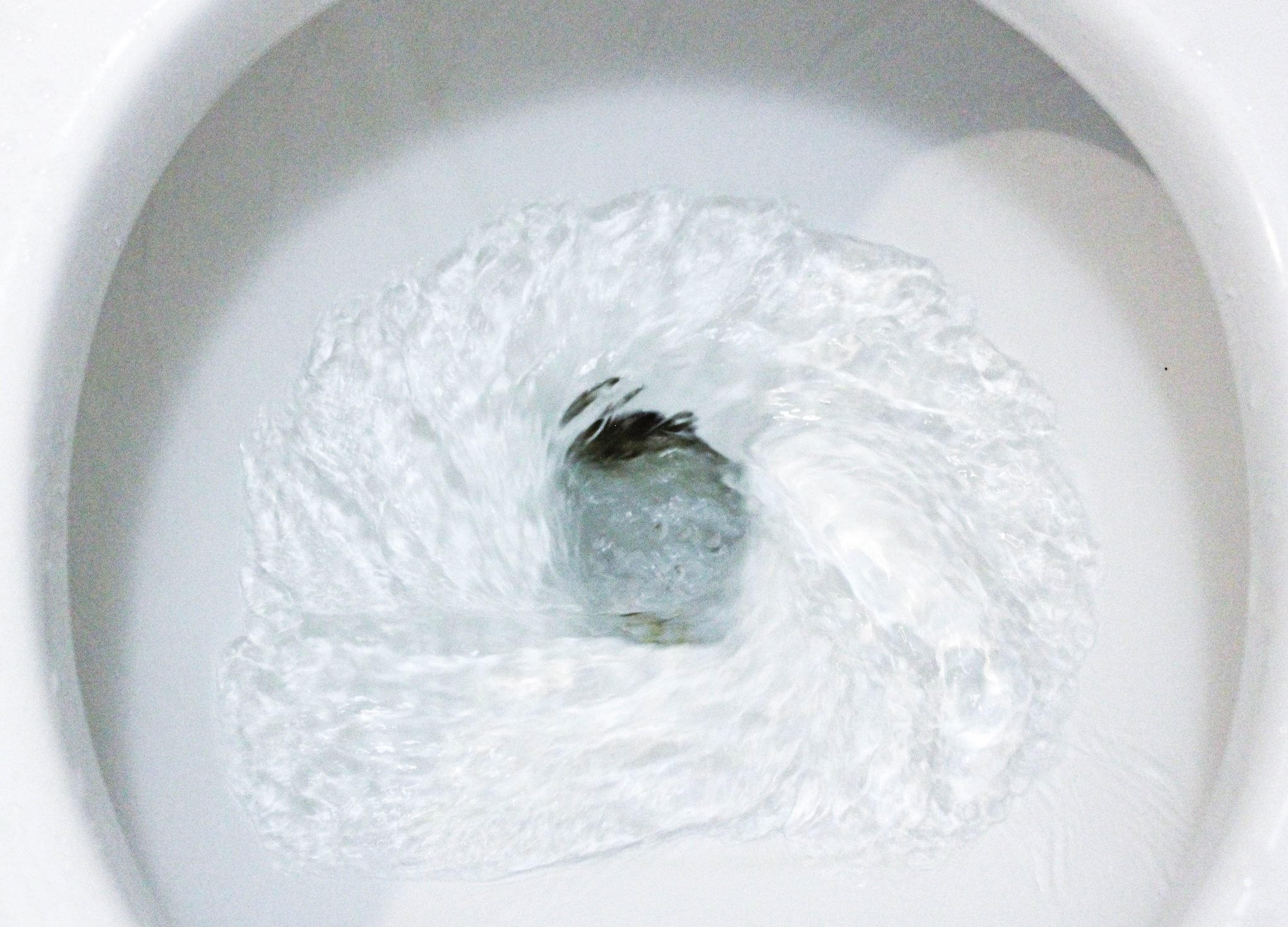 selective focus close up flushing toilet bowl for sanitary