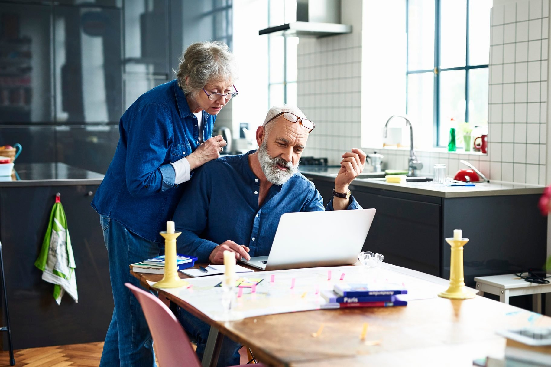 Senior couple planing vacation with map and laptop on table