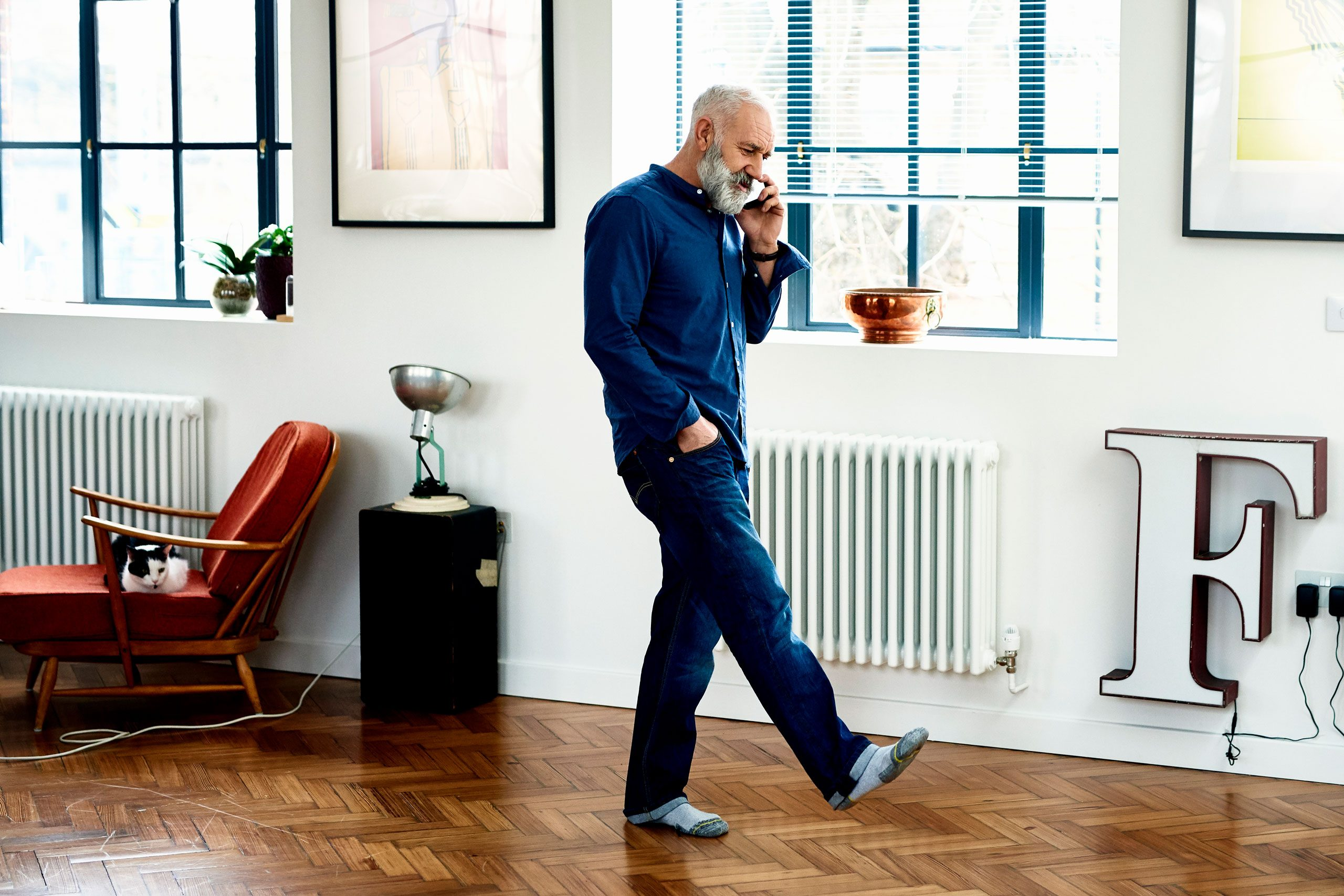 Hipster senior man on cell phone in funky apartment
