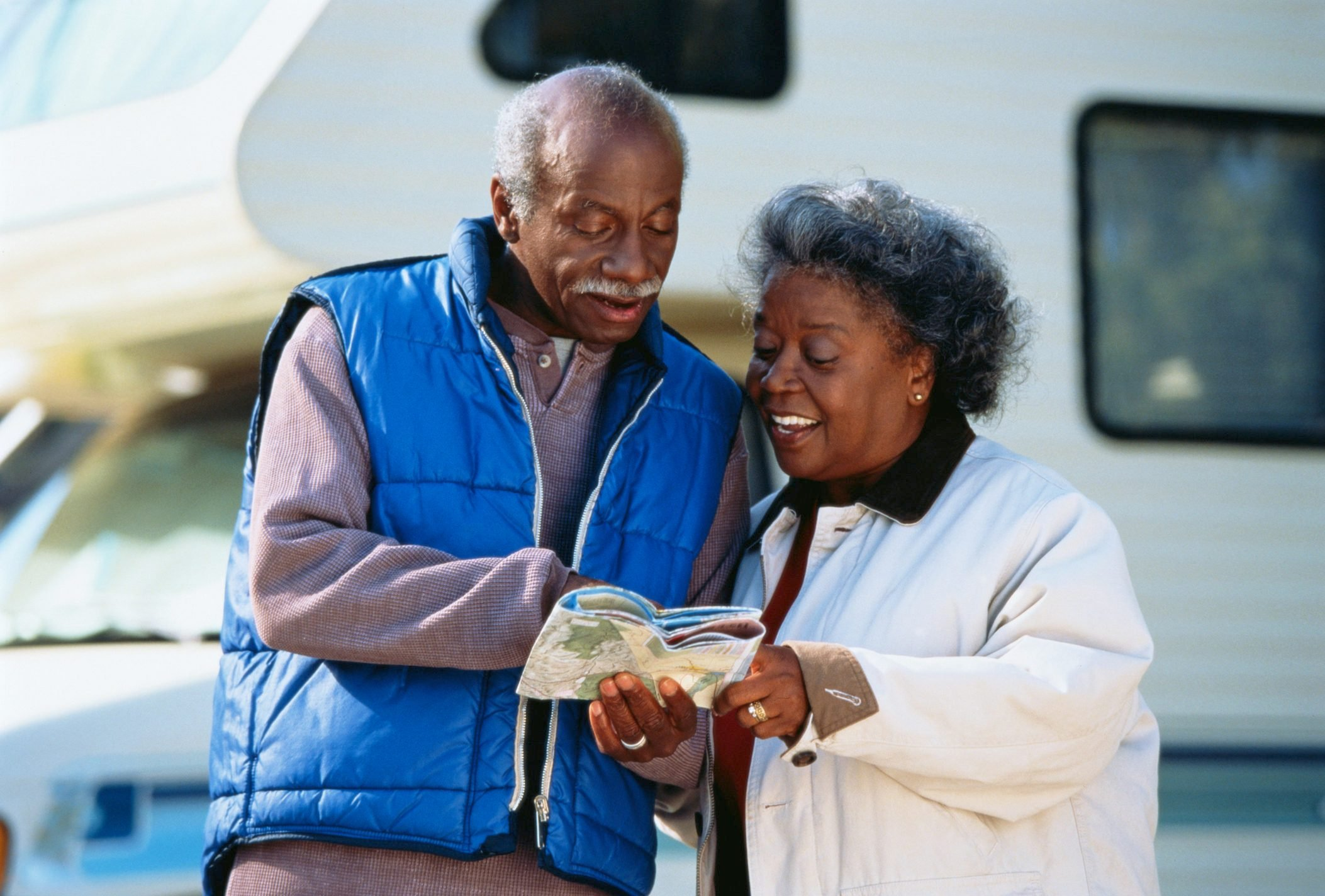 Mature couple by camper van looking at map