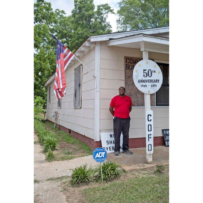 "Glen Cotton standing outside a ""shotgun house"""