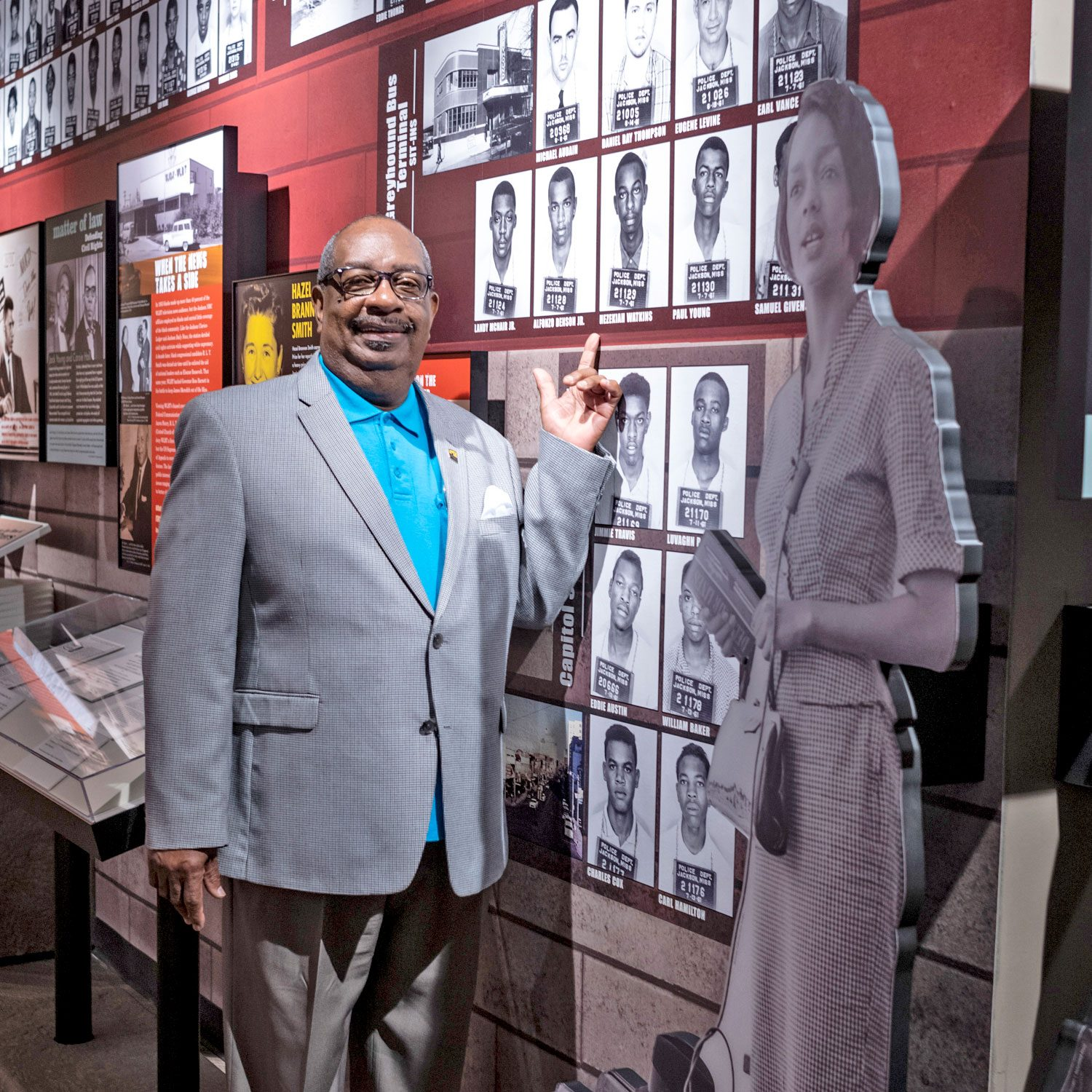 """Hezekiah """"Heck"""" Watkins pointing to his mugshot on the wall of the musuem"""