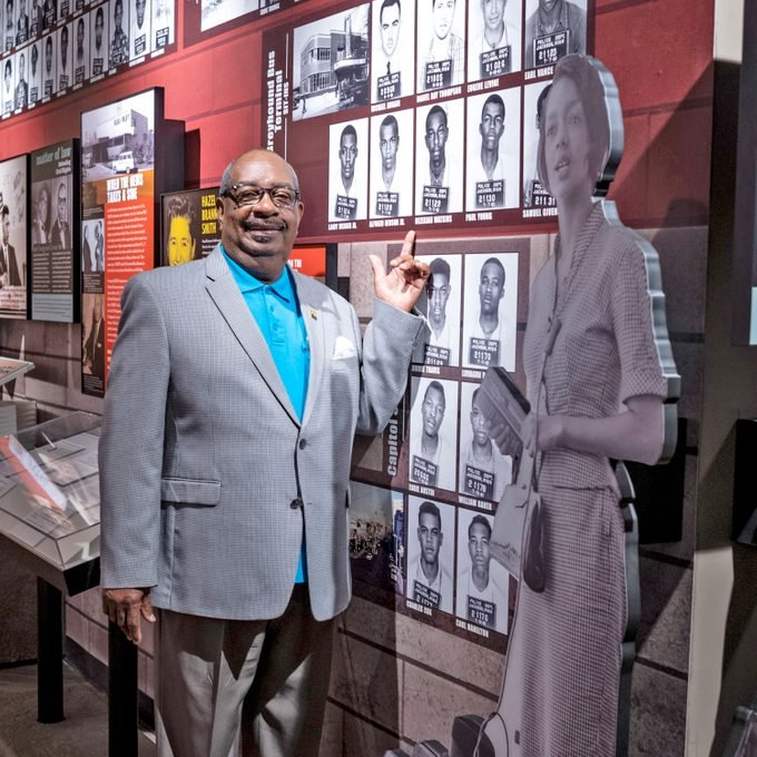 "Hezekiah ""Heck"" Watkins pointing to his mugshot on the wall of the musuem"