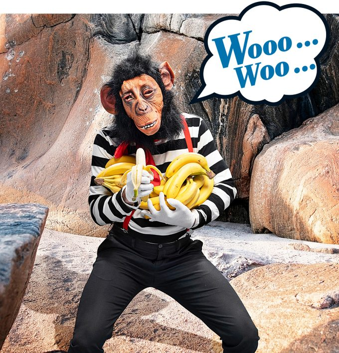 a monkey in a mime outfilt holding bunches of bananas