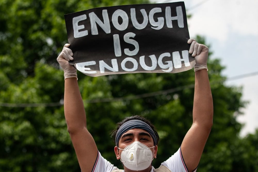 A protester holds a placard saying ' enough is enough' as...