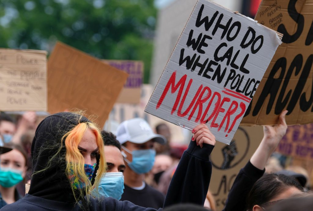 A protester holds a placard saying 'Who Do We Call When...