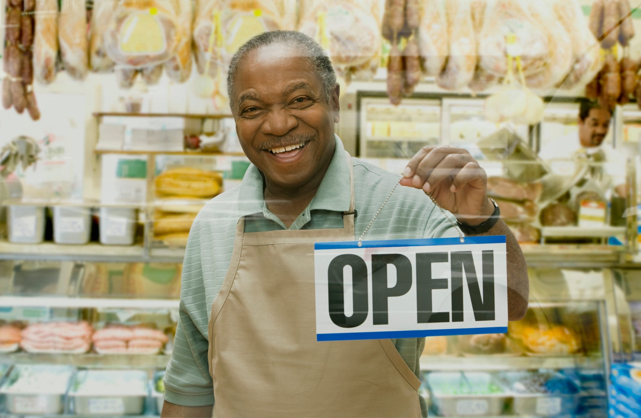 """African butcher holding """"""""Open"""""""" sign"""