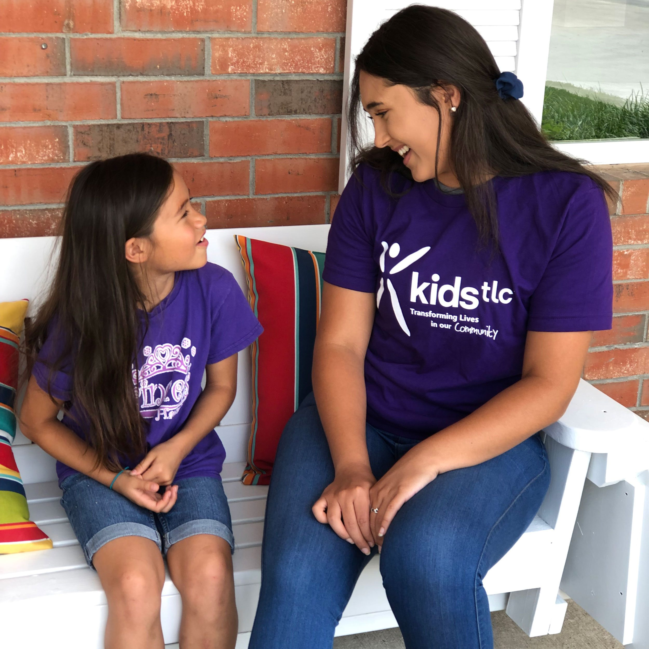 woman in KidsTLC shirt with a girl on a bench