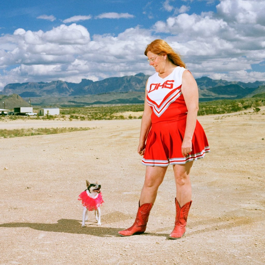 adult cheerleader and chihuahua stand in the desert in uniform