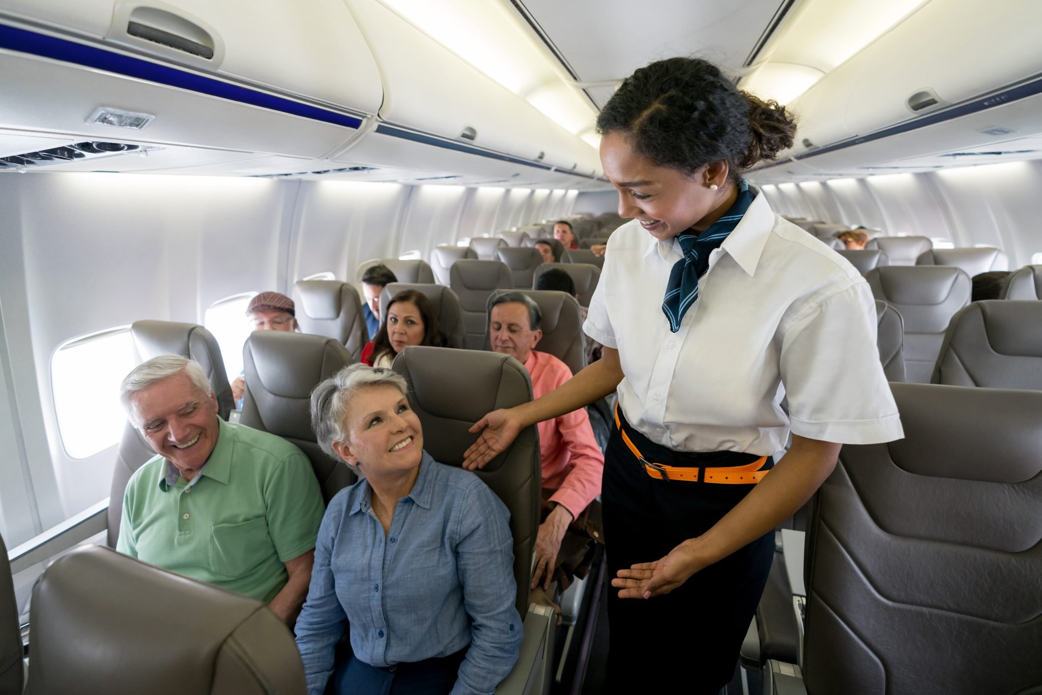 Flight attendant checking on a senior couple in an airplane
