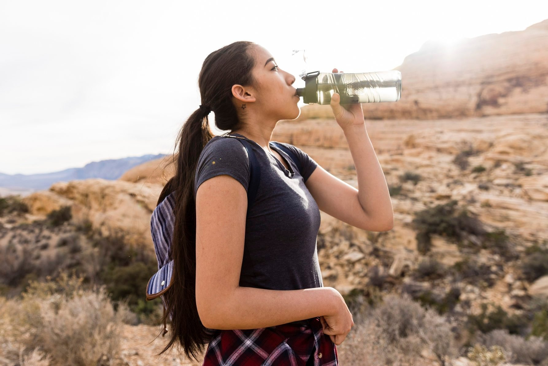 Woman with backpack drinking water while standing by rock formation against clear sky