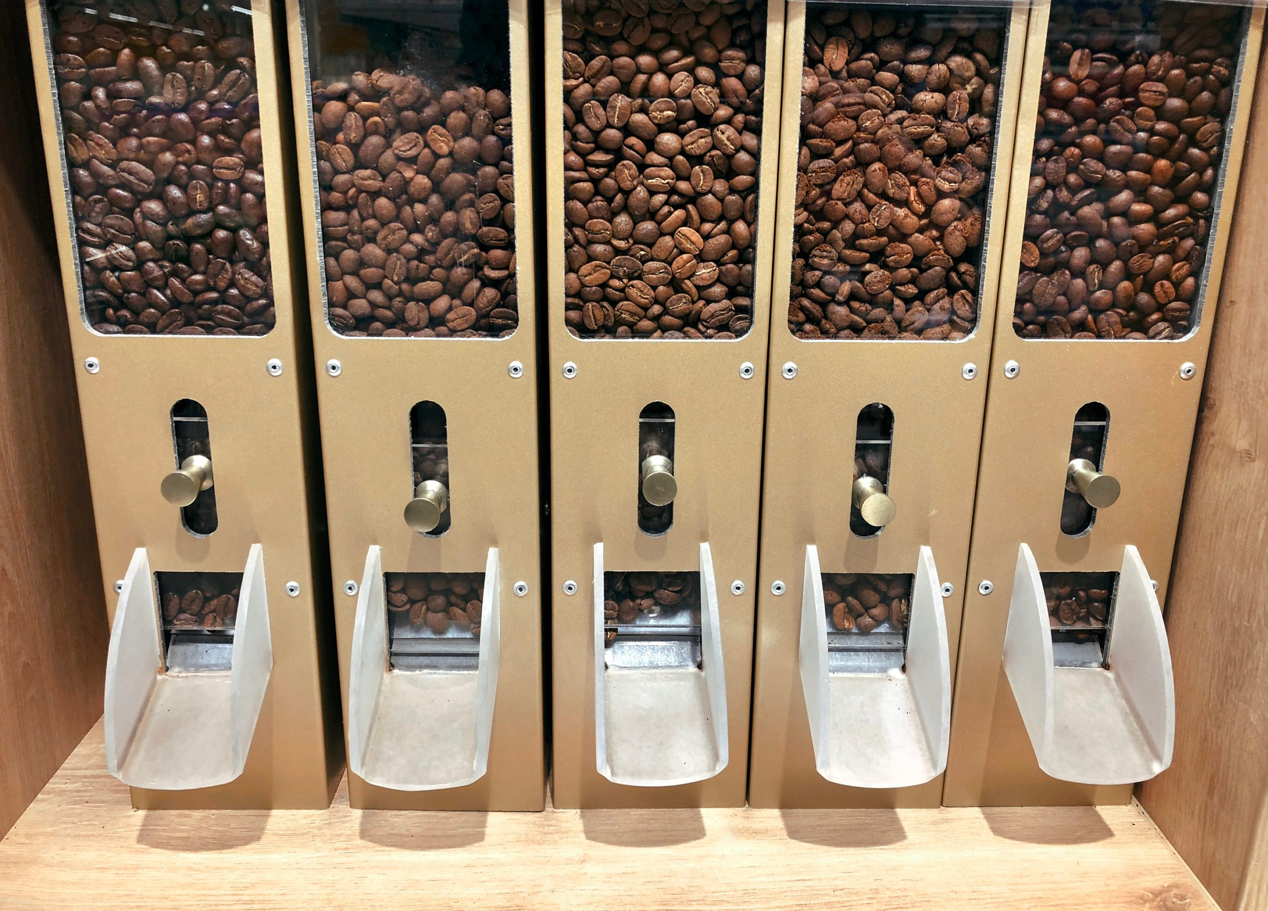 Coffee beans in containers dispensers for self-service in supermarket