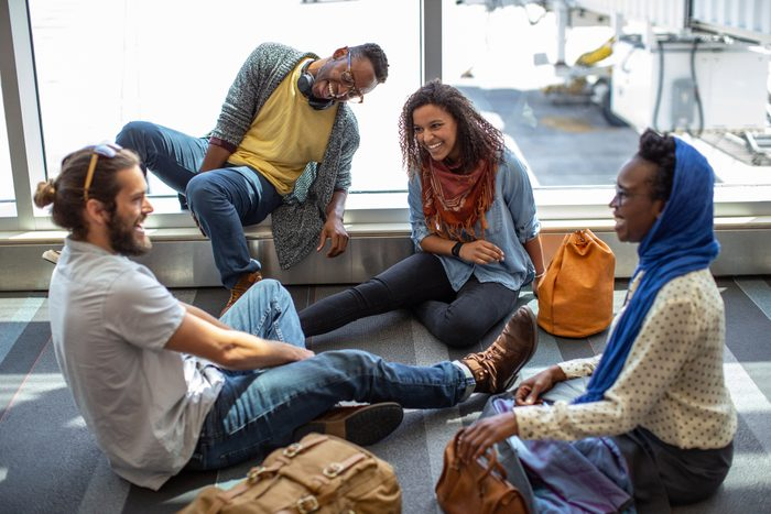 Diverse group of Hipster friends talk and laugh while waiting for flight at airport terminal gate.