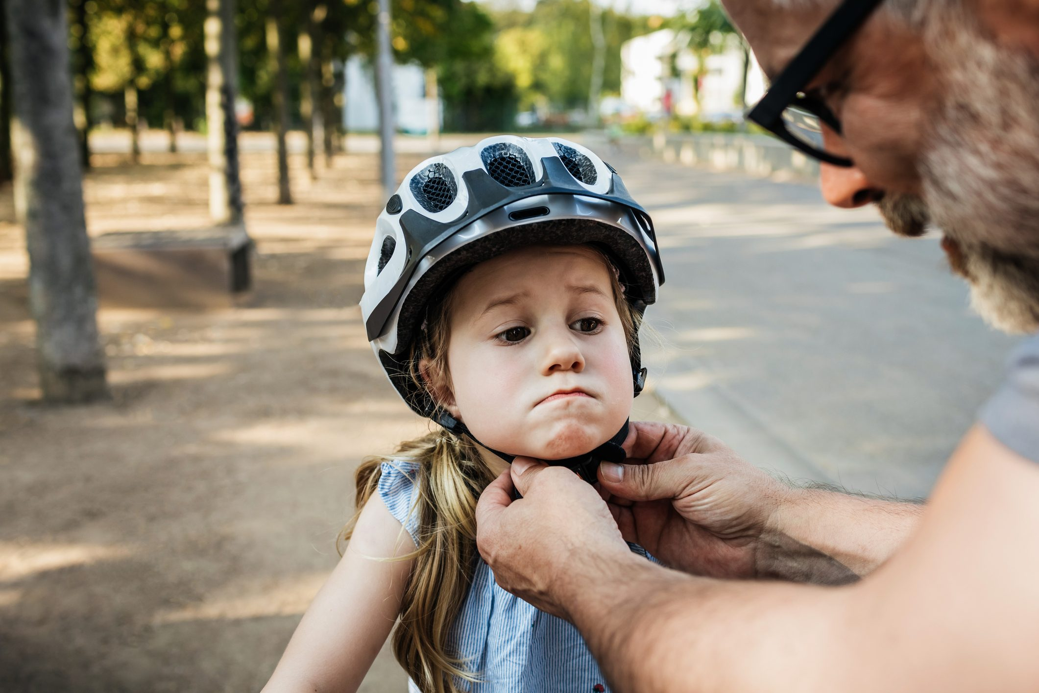Grandpa Doing Up Granddaughter's Crash Helmet