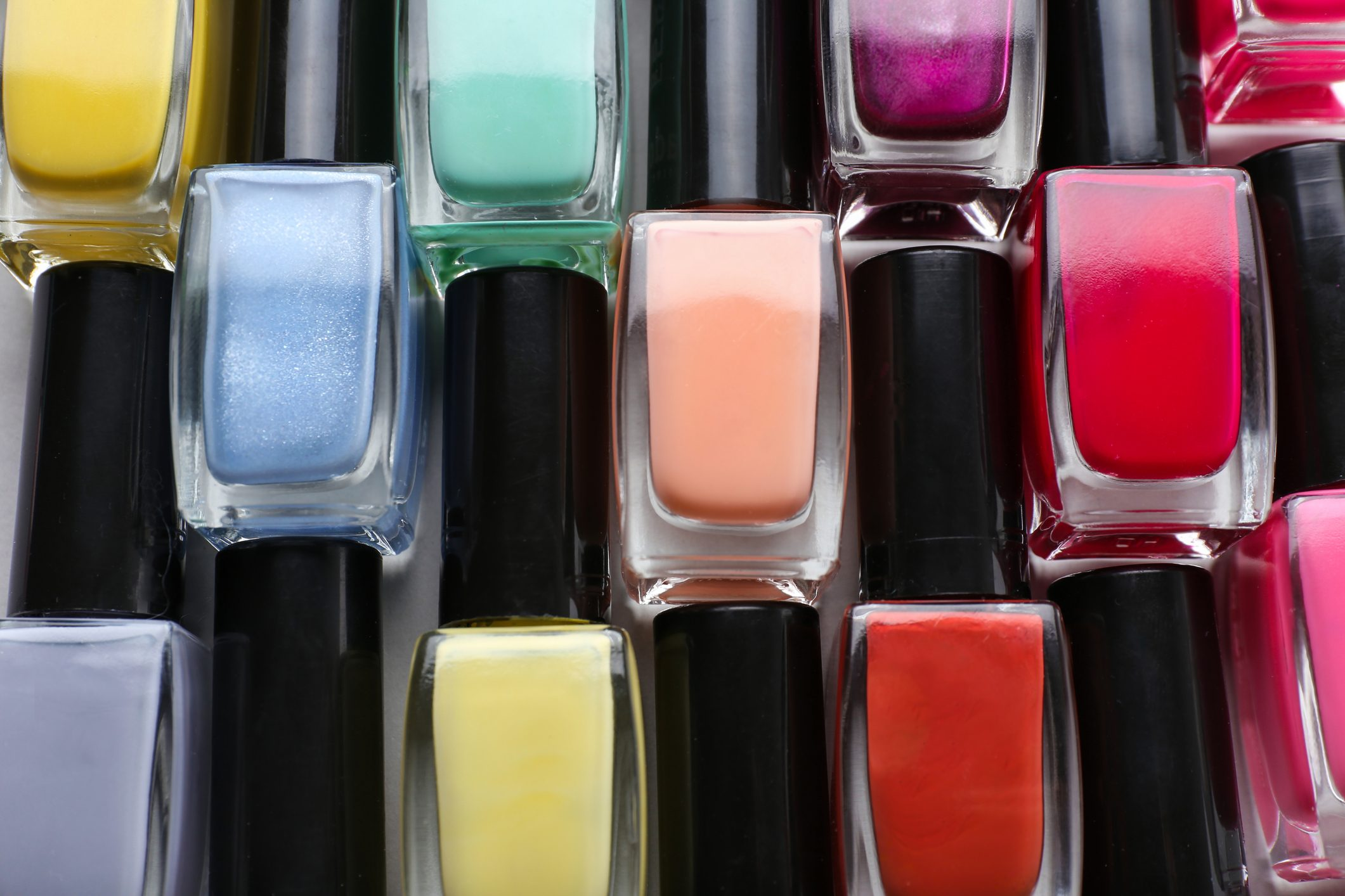 Bottles of colorful nail polishes on table, closeup