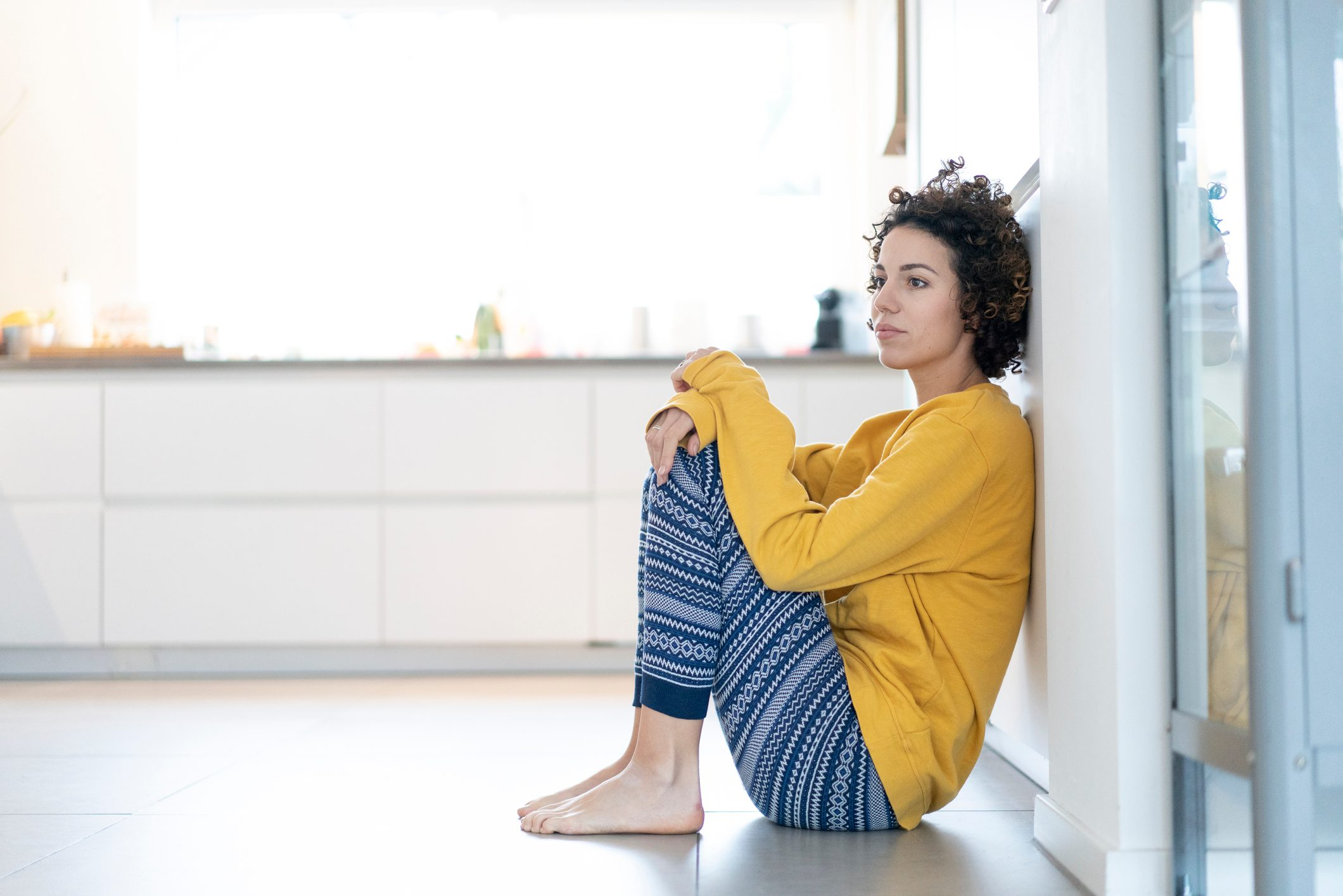 Serious woman sitting on floor leaning against a wall at home