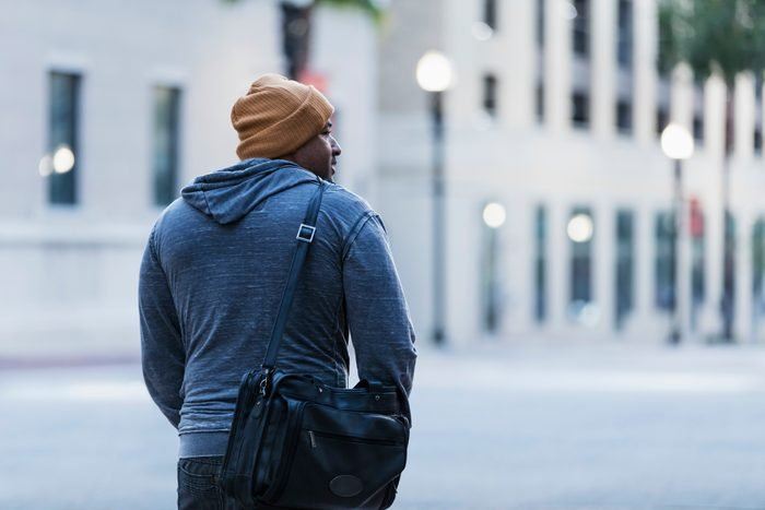 Rear view of mature Hispanic man walking in city