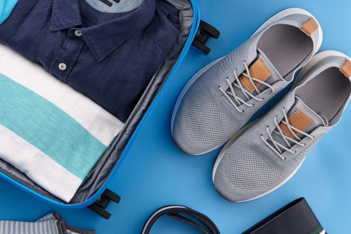 Travel suitcase with clothes on blue background