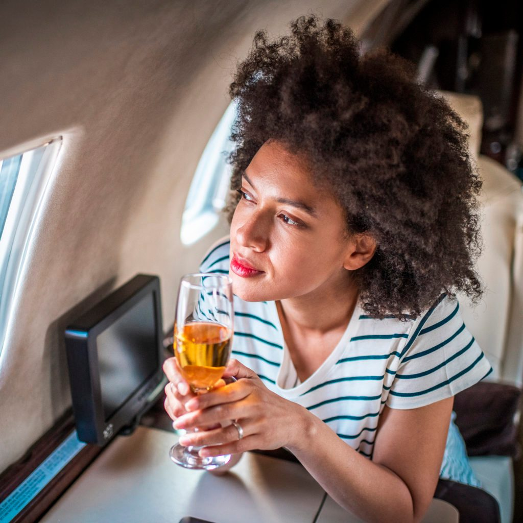 Rich, fashionable afro-american woman looking the window of a private airplane while drinking white wine from a flute