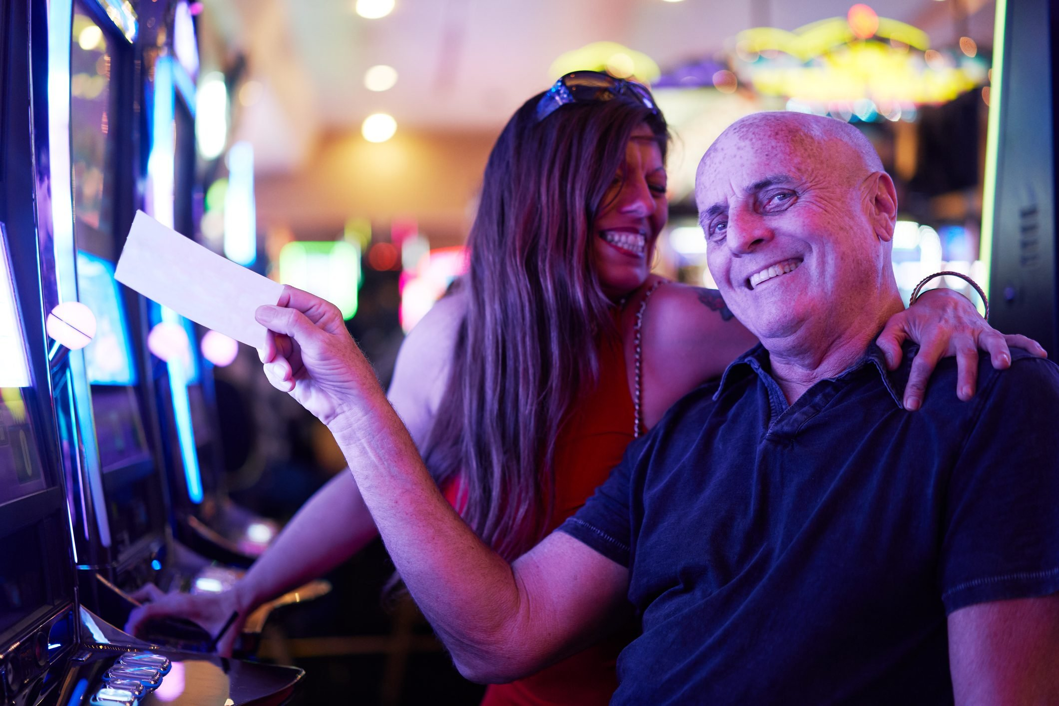 happy mature couple with payout ticket at casino