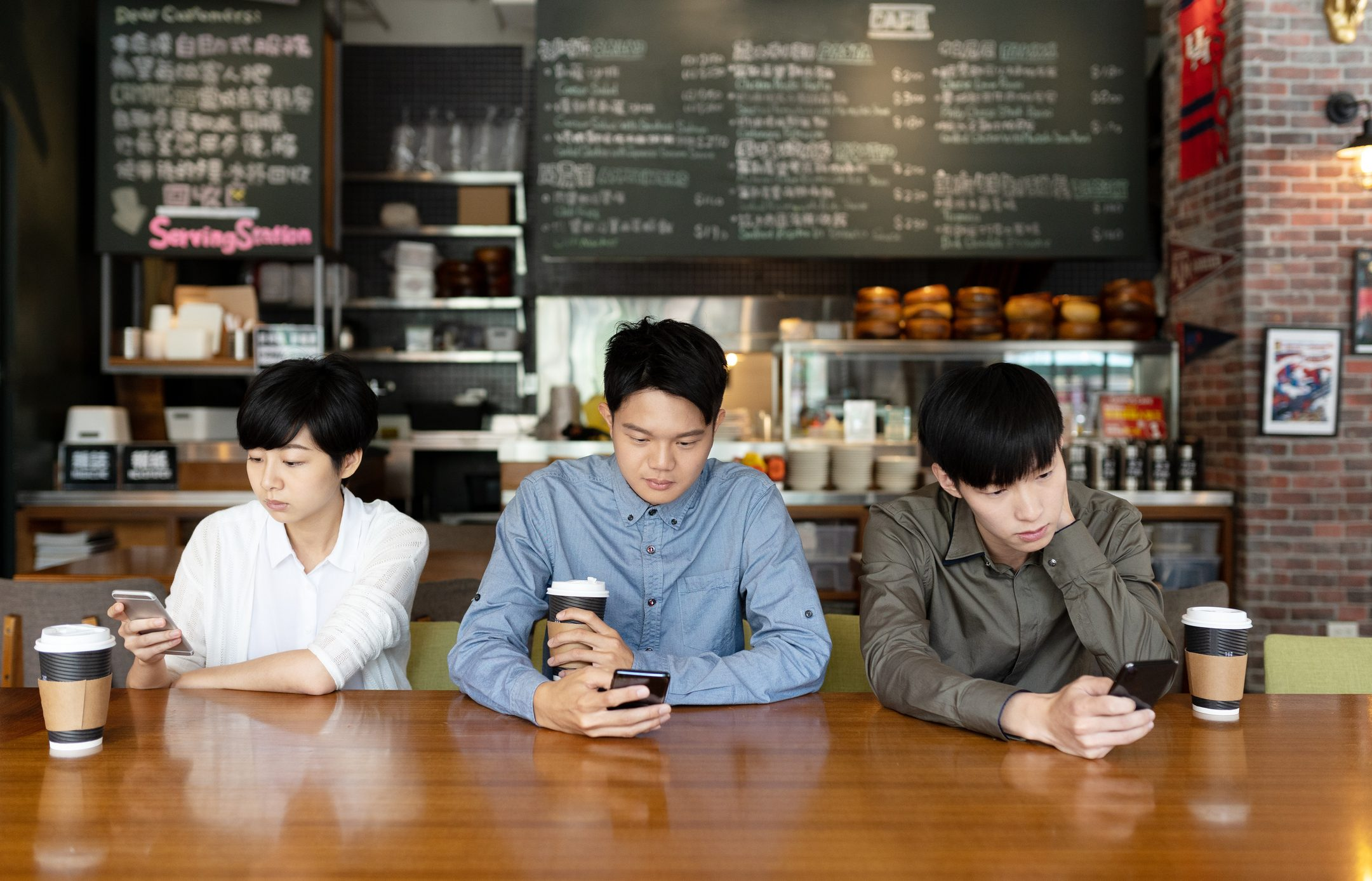 three asian people looking mobile phone