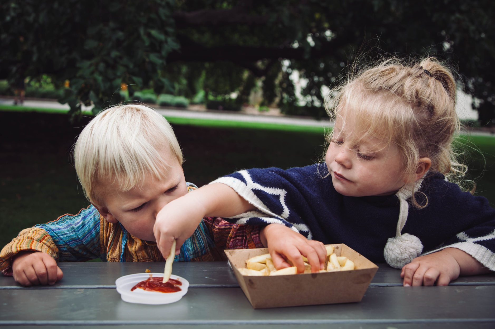 Two toddlers sharing hot chips and tomato sauce at a picnic in the park