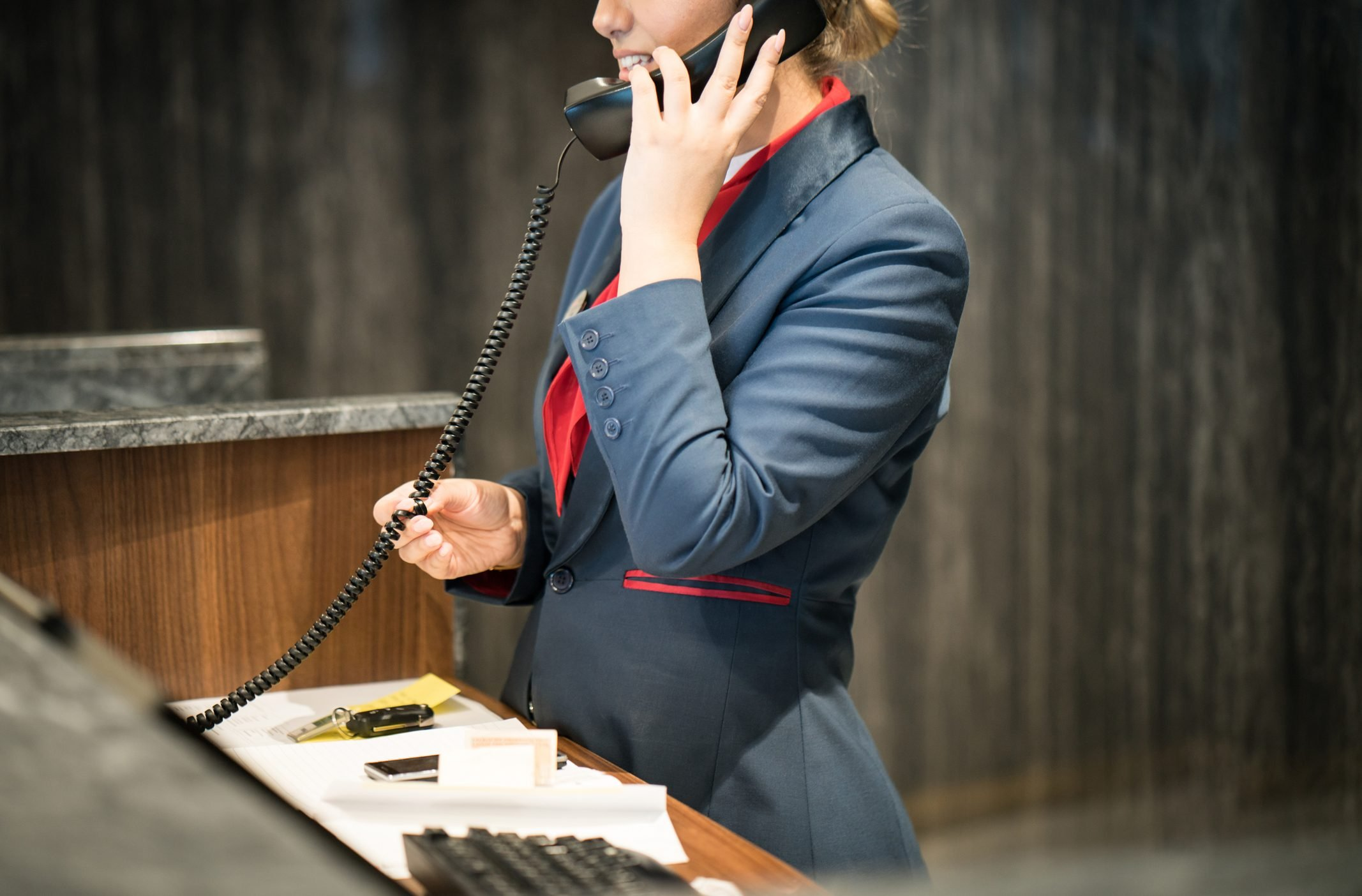 Nervous Hotel Receptionist Talking on Phone