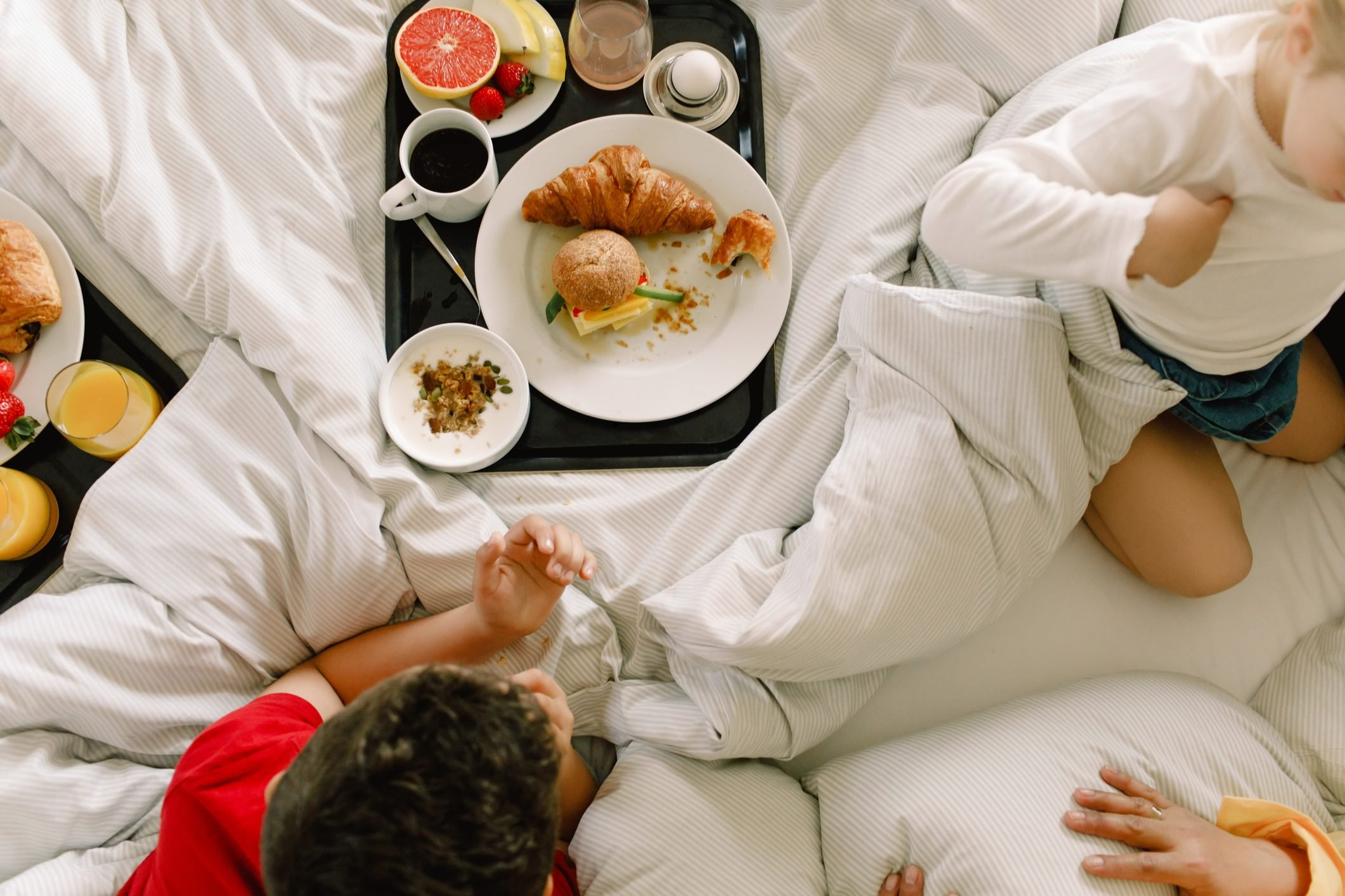 Directly above shot of family having breakfast on bed in hotel