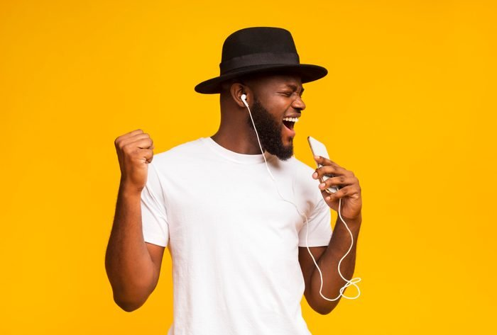 Happy african man in hat singing into smartphone like microphone