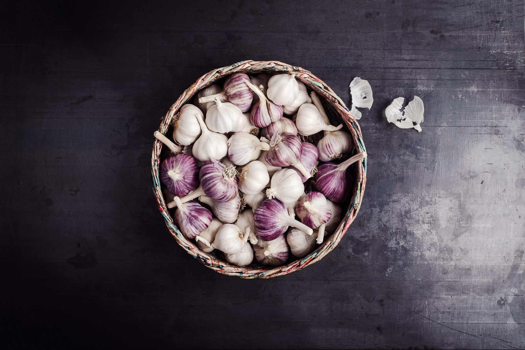 Fresh purple garlic in basket made from newsprint papers