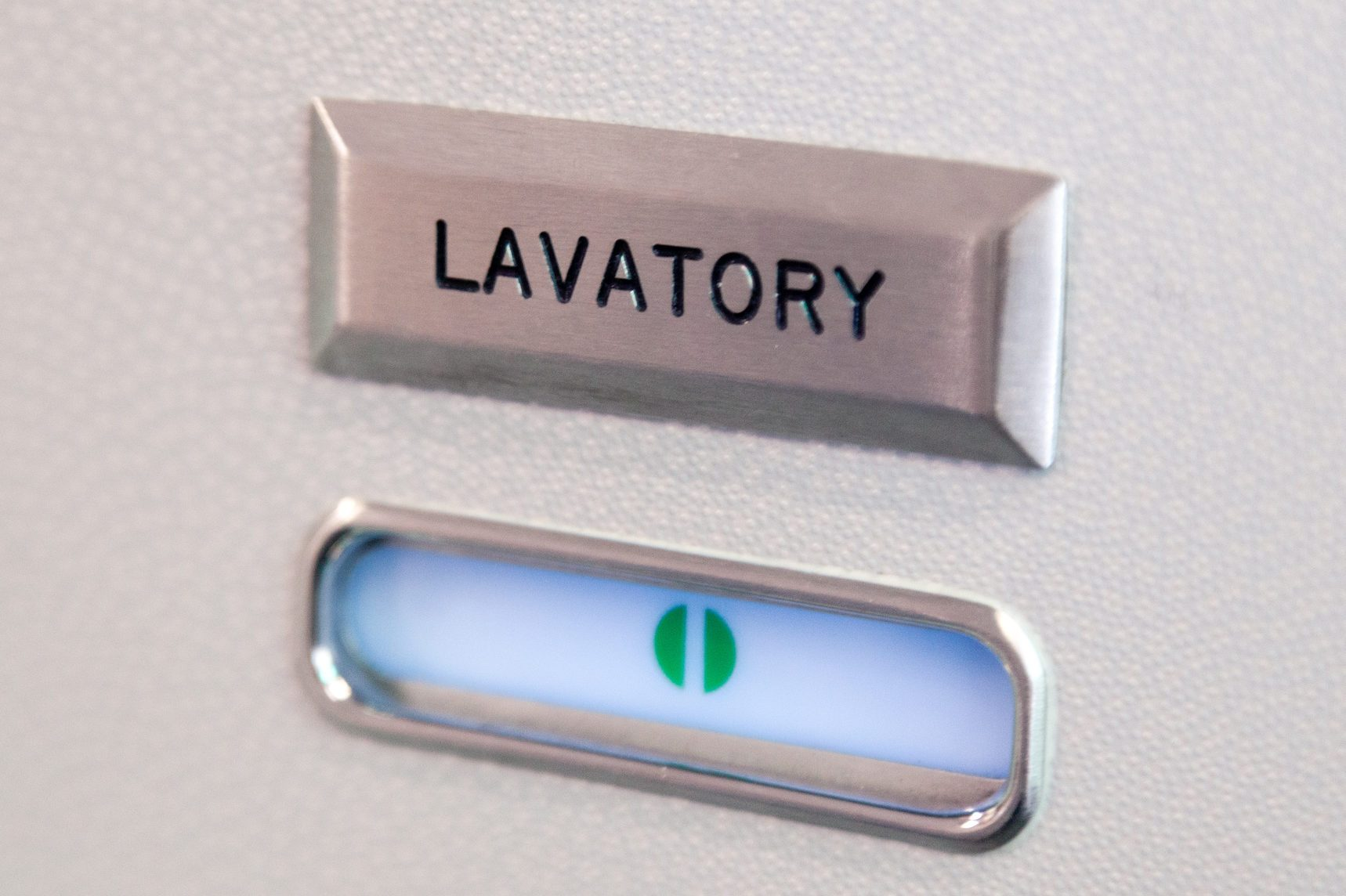 Vacant green sign, vacant symbol on an airplane lavatory door. Raised, brushed metal lavatory sign, recessed plastic vacant sign. Toilet room, wc, closet on airplane board
