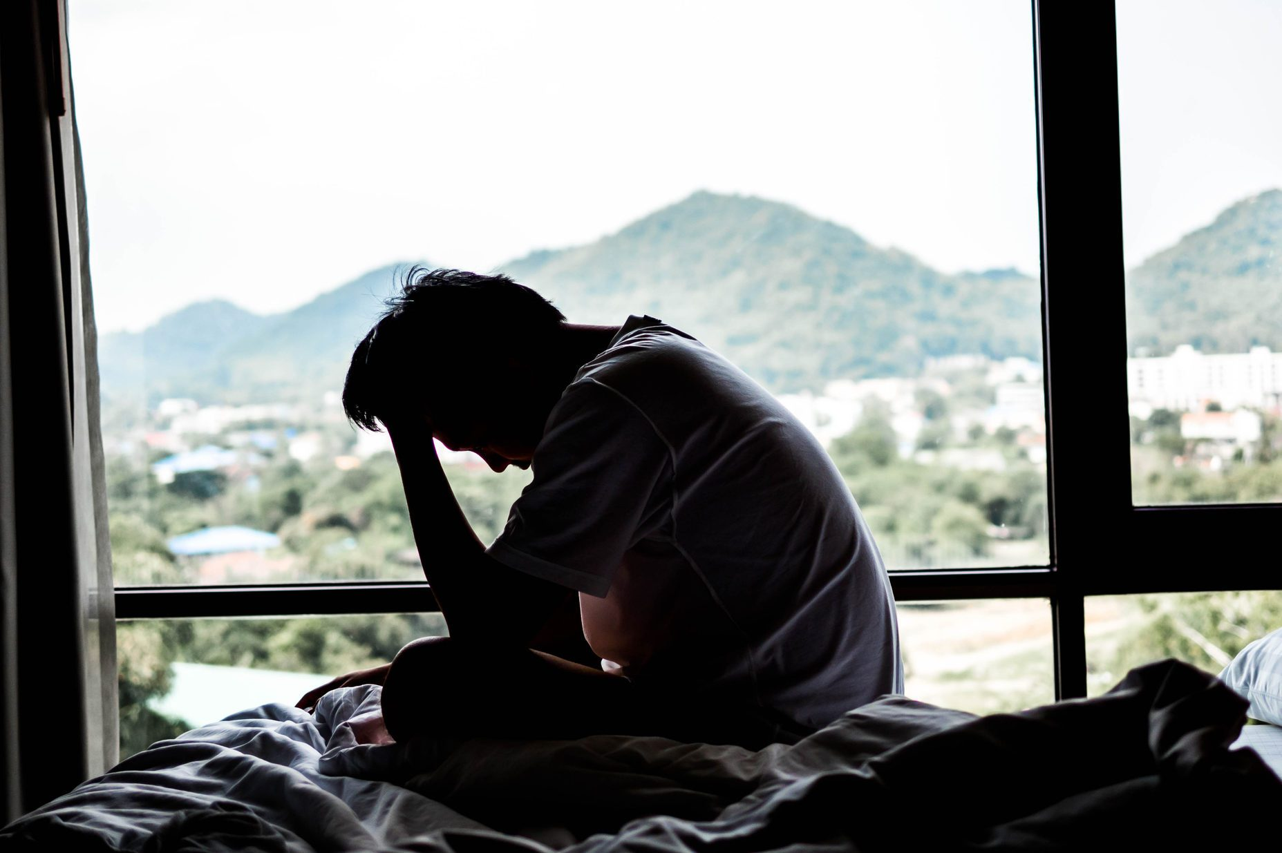 Side View Of Sad Man Sitting On Bed By Window