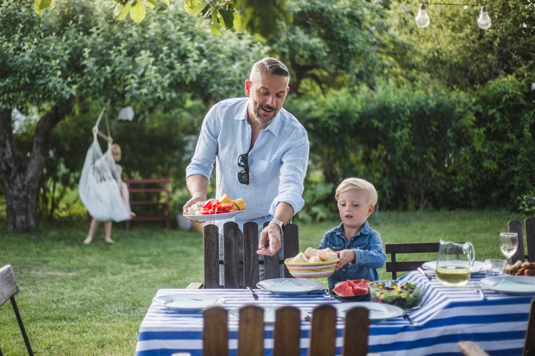 Mature father directing son with food plate while pointing at table in yard