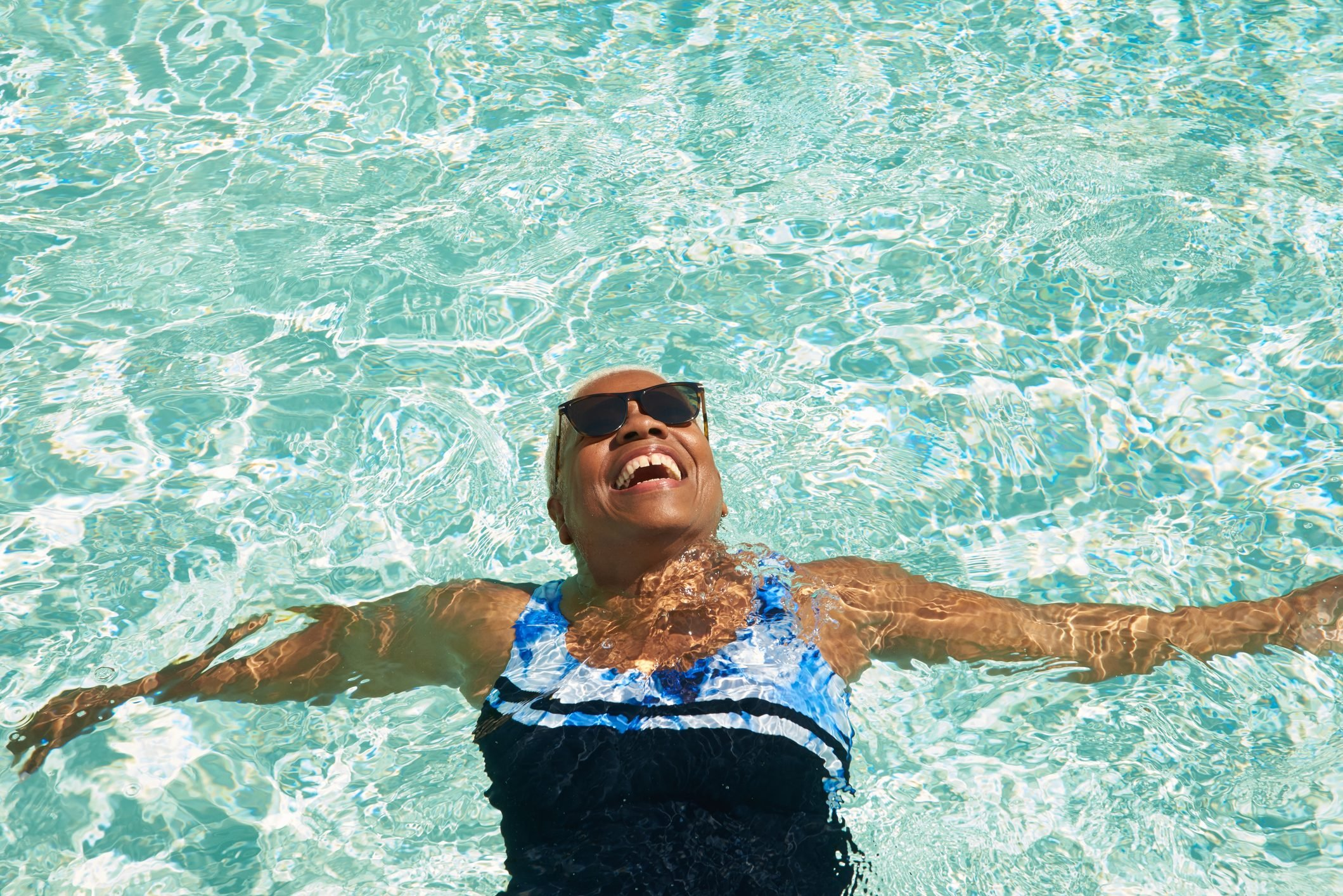A mature woman relaxes in a swimming pool