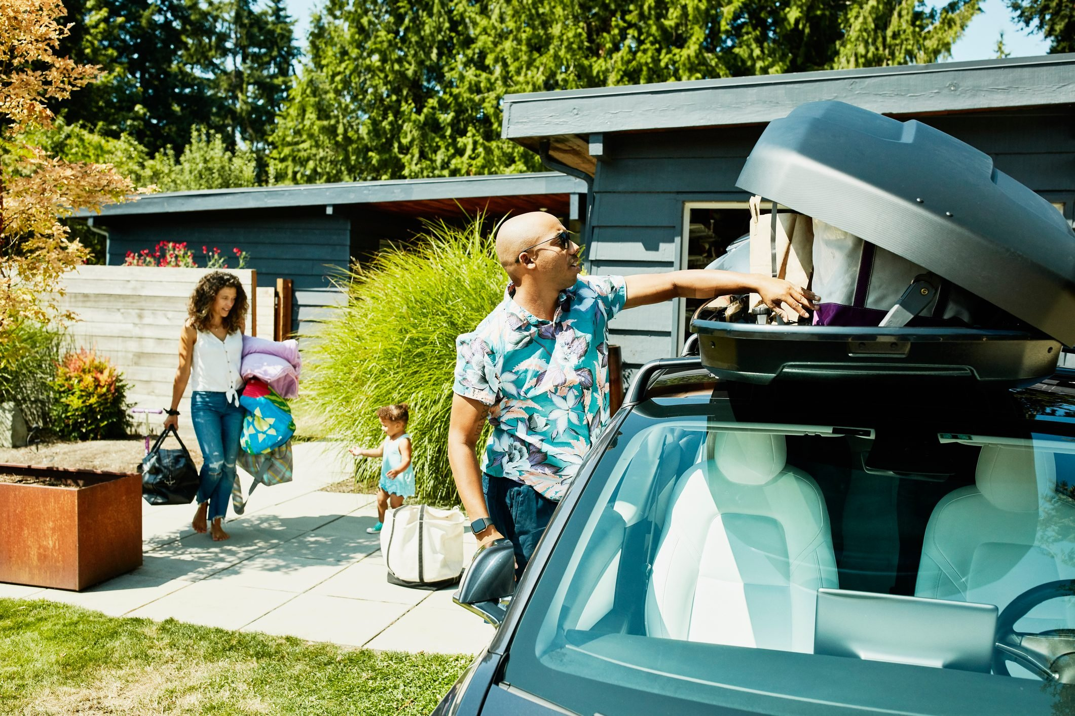 Family loading luggage into car top box before road trip