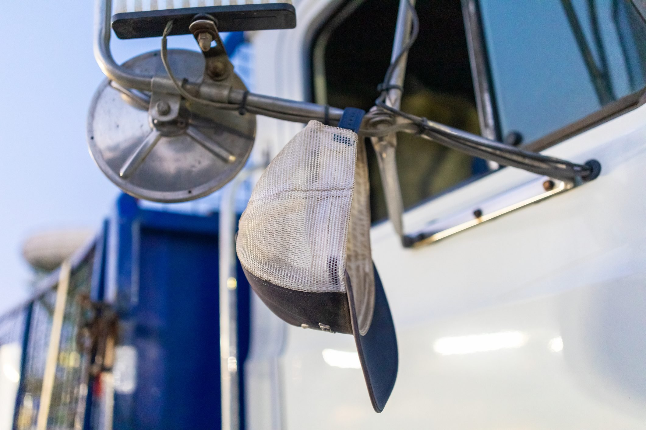 Trucker's Hat Hanging Off Side Mirror Of Prime Mover