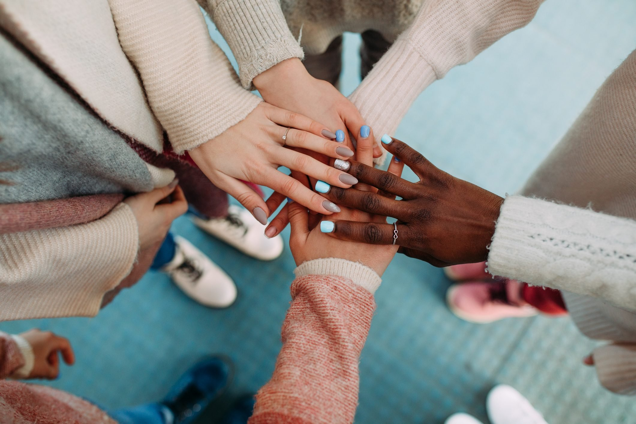 Hands of women of different races touch each other closeup.