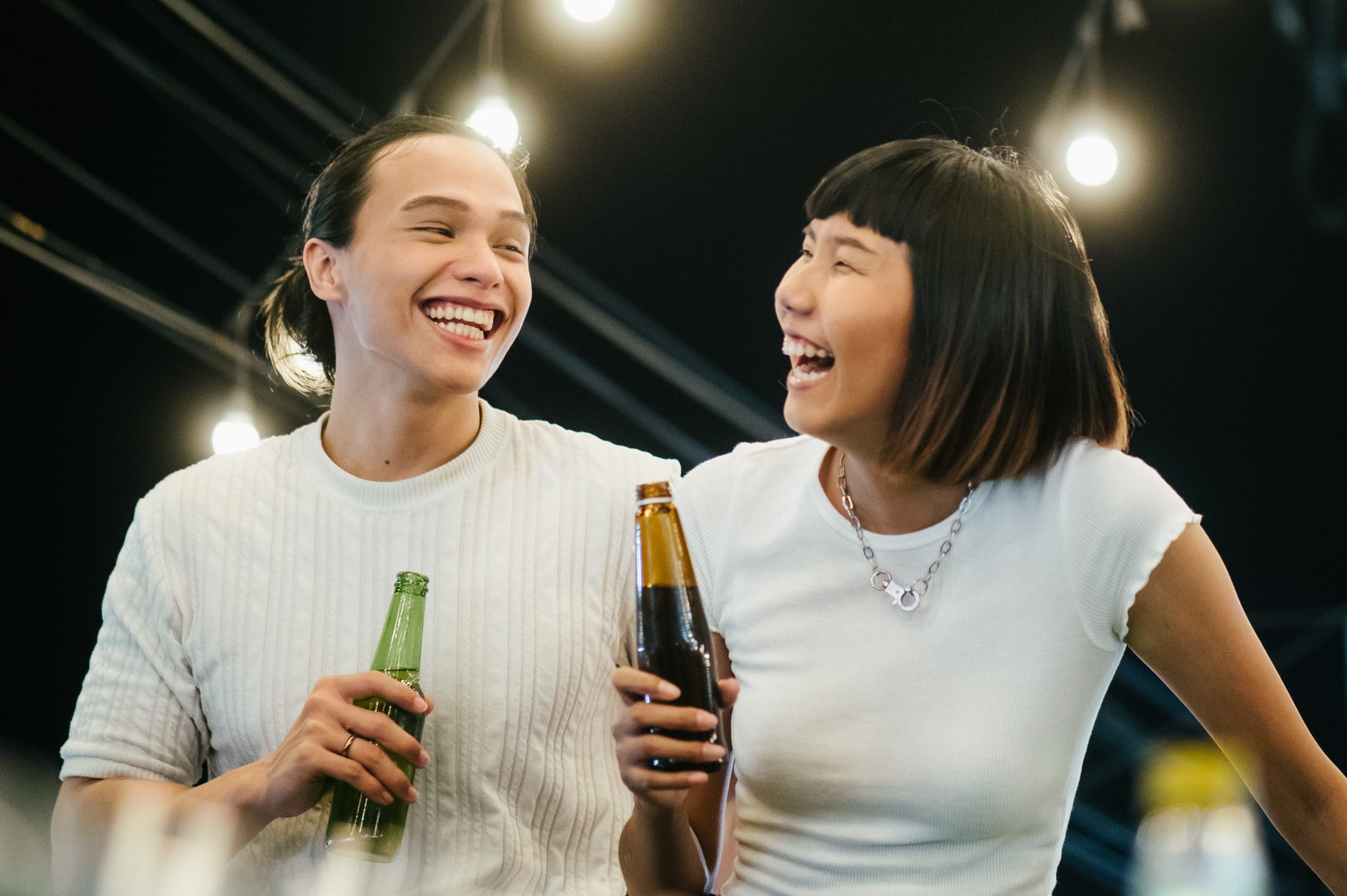Young asian couple toasting with beer at rooftop party