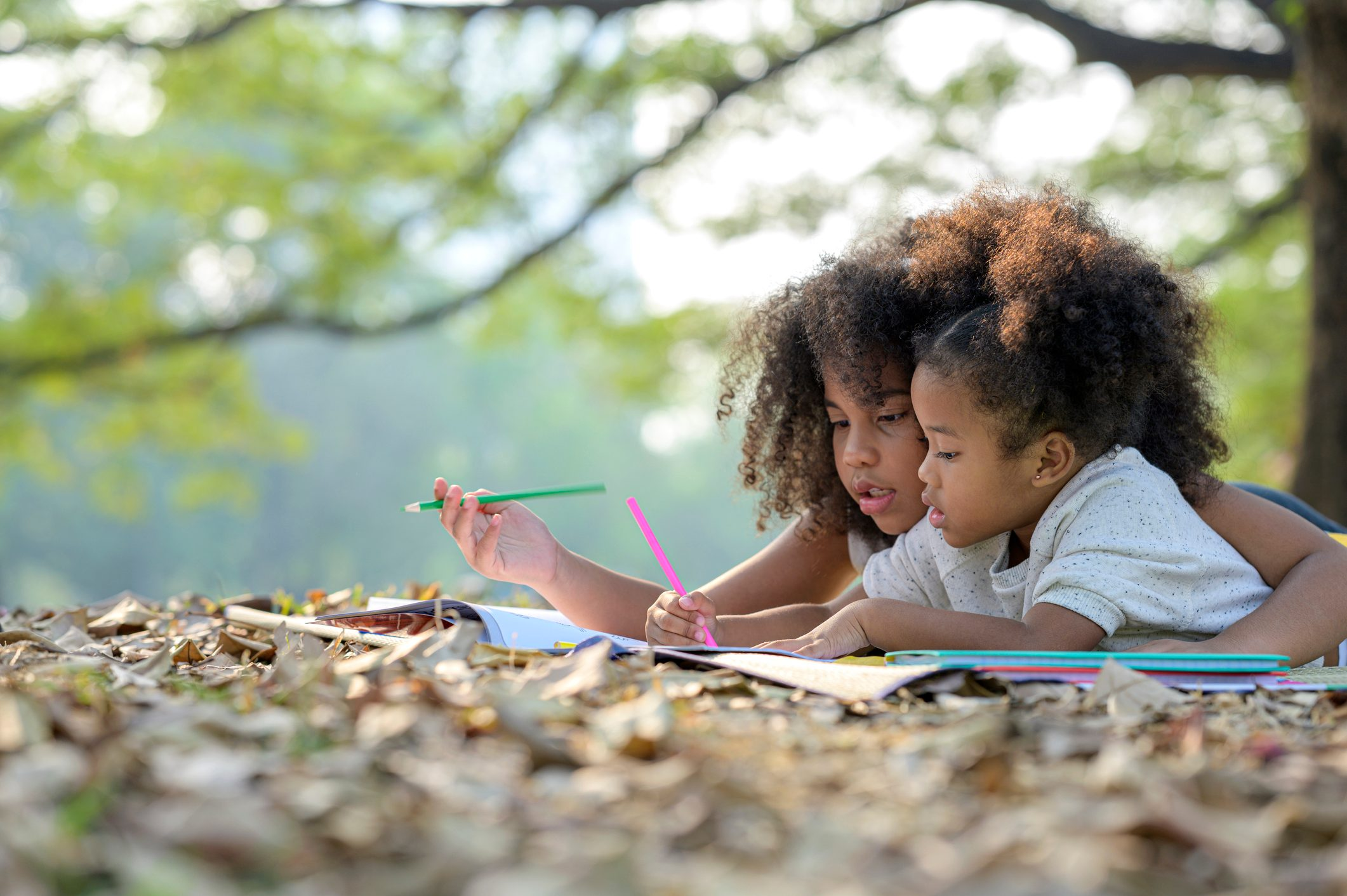 Two adorable cute Afro girls, lying in the park, reading a book and drawing. Educating themselves concept.