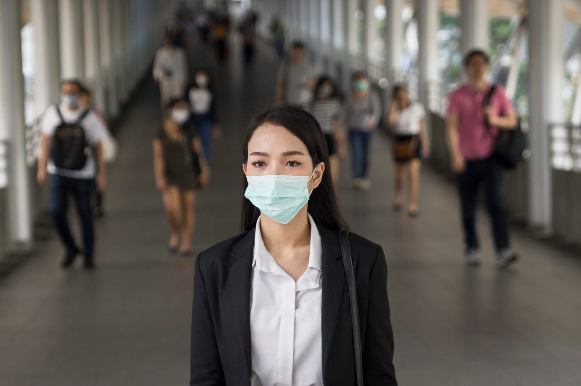 Asian woman with protective face mask in the urban bridge in city against crowd of people
