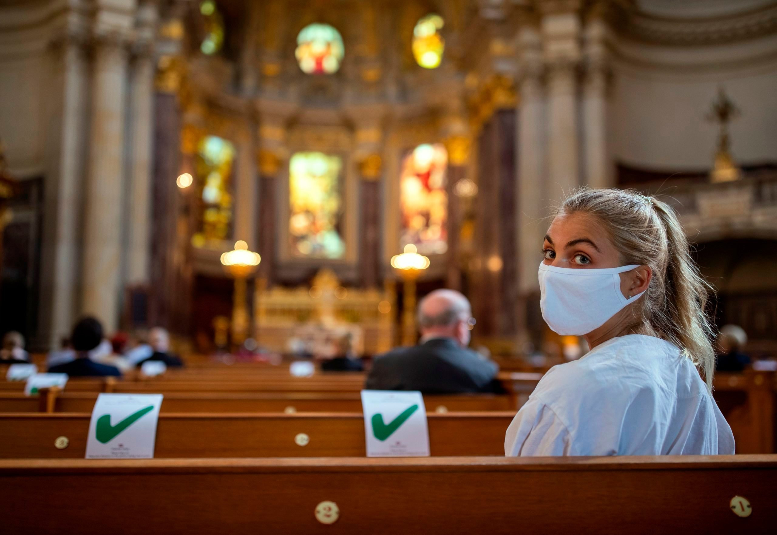 A woman wearing a protective face mask attends a Sunday service at the Berliner Dom cathedral in Berlin on May 10, 2020, amid the Covid-19 coronavirus pandemic. - The German capital's Protestant Cathedral reopened for worshippers on Sunday after being online only for two months, due to restrictions and social distancing rules implemented to limit the spread of the virus.